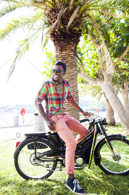 BERMUDA, Hamilton. - September 12, 2015:  Chef Marcus Samuelsson on a vintage scooter in Barr's Bay Park located in downtown Hamilton. The Hamilton Harbour is in the background.