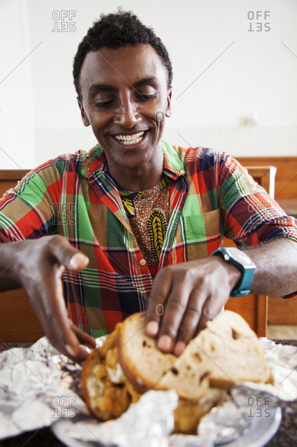 BERMUDA. St. George. - September 12, 2015:  Chef Marcus Samuelsson about to eat a fish sandwich at Art Mel's Spicy Dicey Restaurant in St. George.