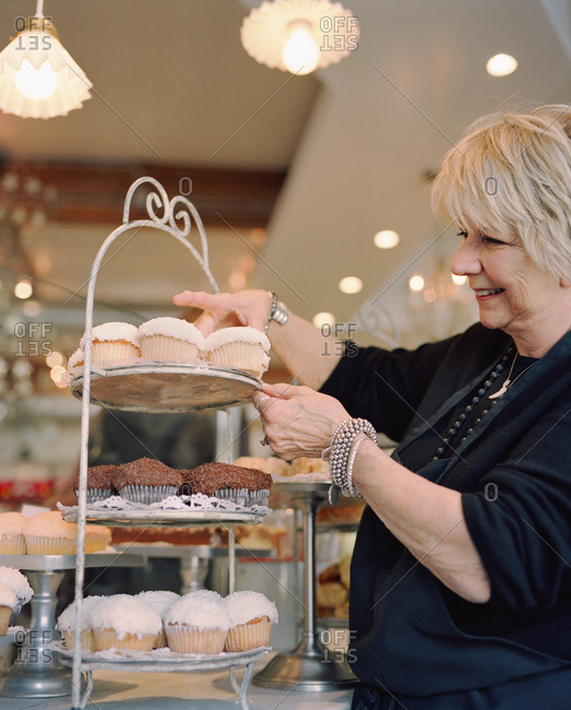 USA, California, Los Angeles, - August 12, 2010:  Owner Joan McNamara arranging cupcakes in her cafe Joan's On Third.