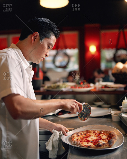 USA, California, Los Angeles, - August 12, 2010:  chef cutting pizza at Pizzeria Mozza restaurant