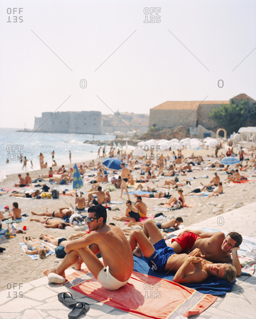 CROATIA, Dubrovnik, Dalmatian Coast,  - September 28, 2010: relaxing at East West Beach with the old city of Dubrovnik in the background.