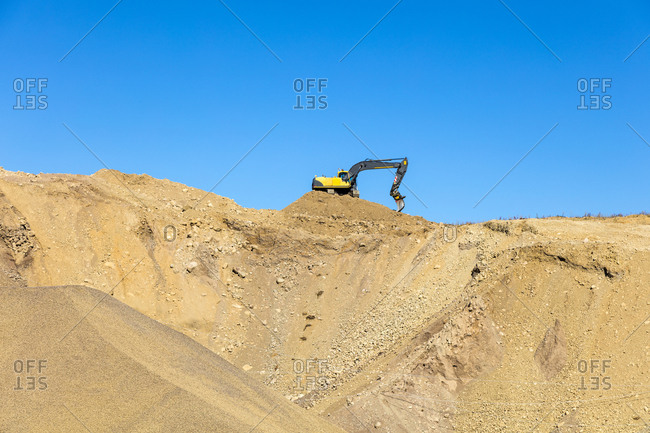 Digger on pile of sand