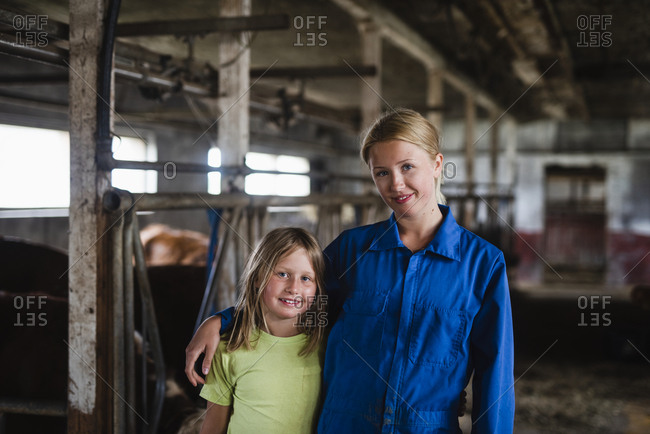 Woman with daughter in cowshed