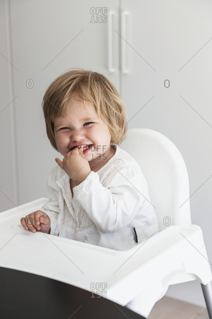 Smiling baby girl on high chair