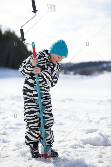 Boy drilling hole in ice