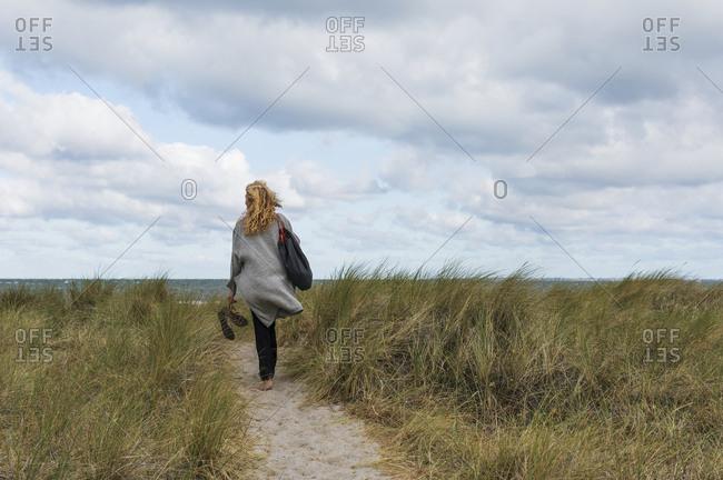 Woman walking towards sea