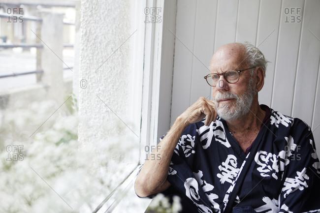 Senior man looking through window
