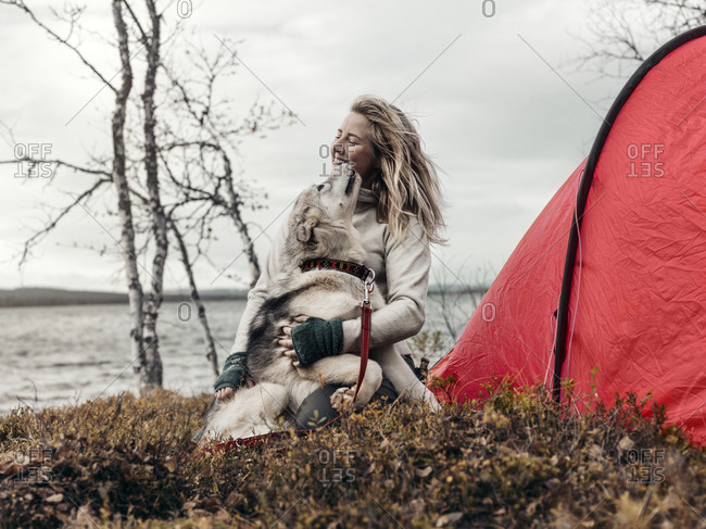Woman with dog in front of tent