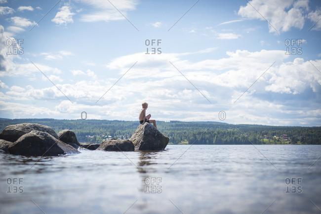 Boy sitting on rock at sea