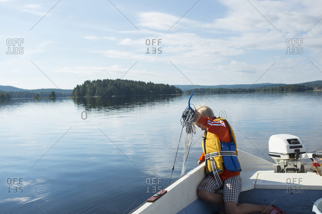 Boy pulling net out of water