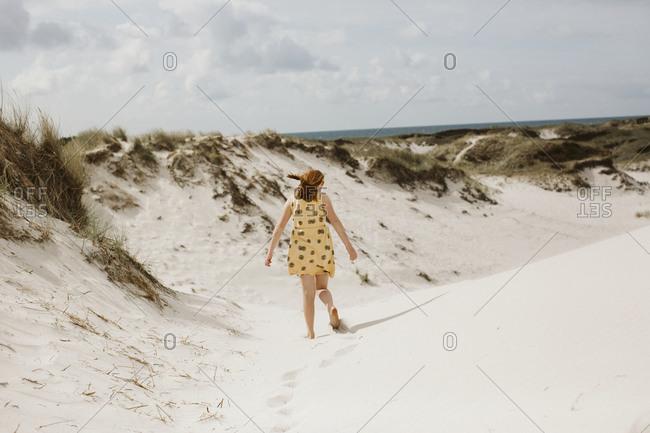 Girl walking on sand dune