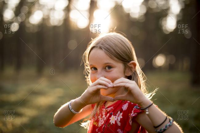 Girl making heart gesture