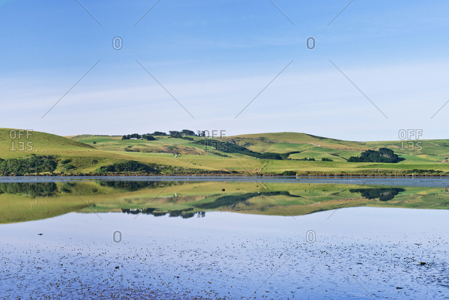 Rural hills reflected in calm estuary,Estuary, Catlins, New Zeland