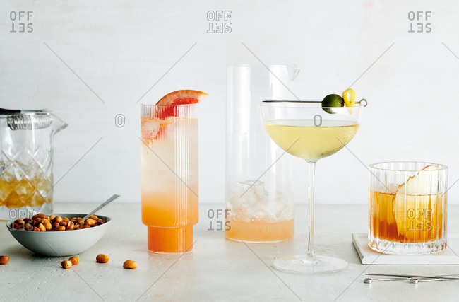 Normandine Club Spritz, Doubting Duck, Old Fashioned and beer nuts on white marble
