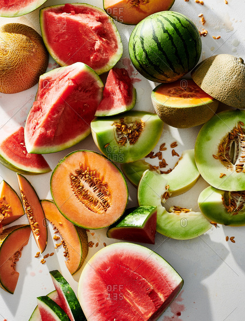A variety of whole and sliced melons on white background