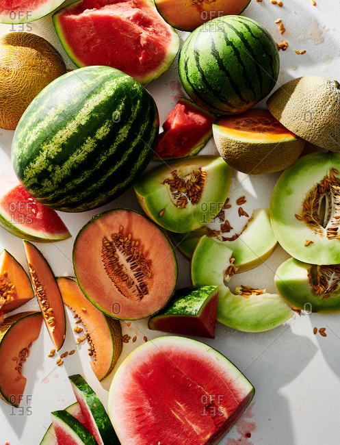 Whole and sliced melons on white background