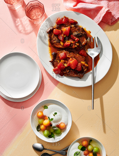 Platter of pork steaks and poached melon on colorful background