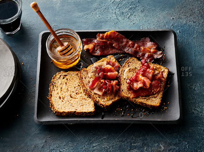 Overhead view of breakfast bruschetta with espresso nib butter and bacon