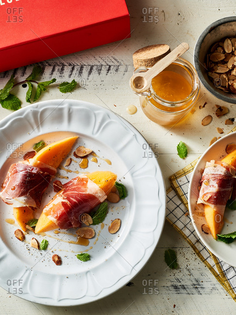 Plate of melon wrapped prosciutto drizzled with honey and toasted almonds