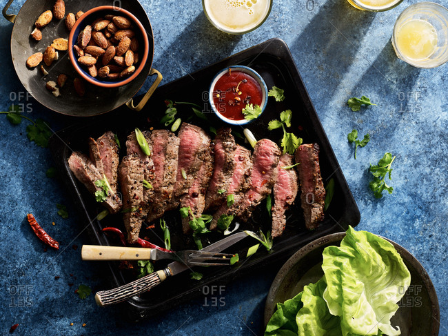 Tray of Korean steak lettuce wraps with sriracha, smoked almonds  and beer