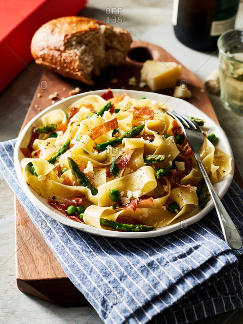 Close-up view of pappardelle pasta with prosciutto, asparagus, spring peas and parmesan
