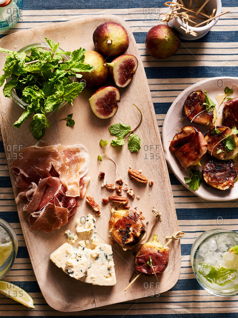Overhead view of cutting board with prosciutto wrapped figs, bleu cheese, and herbs