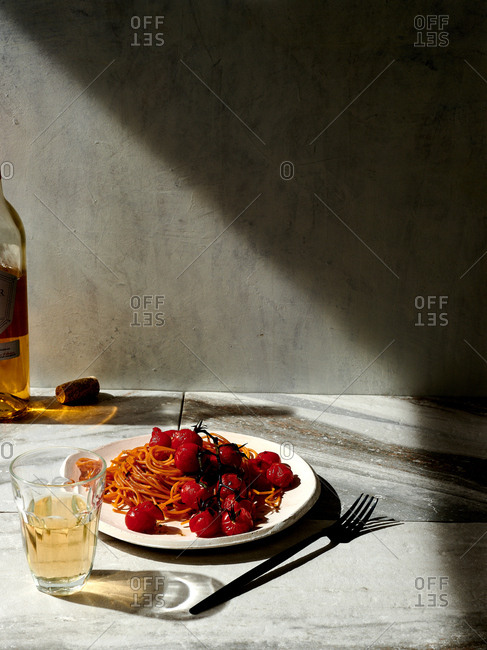 Bowl of tomato pasta and glass of white wine