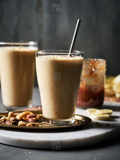 Two nut butter, banana, and jam smoothies with and a tray of nuts