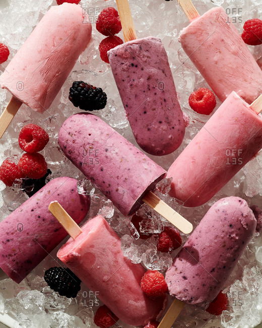 Raspberry and blackberry popsicles on ice