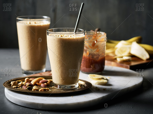 Two peanut butter, banana, and jam smoothies with jam and bananas and a tray of nuts