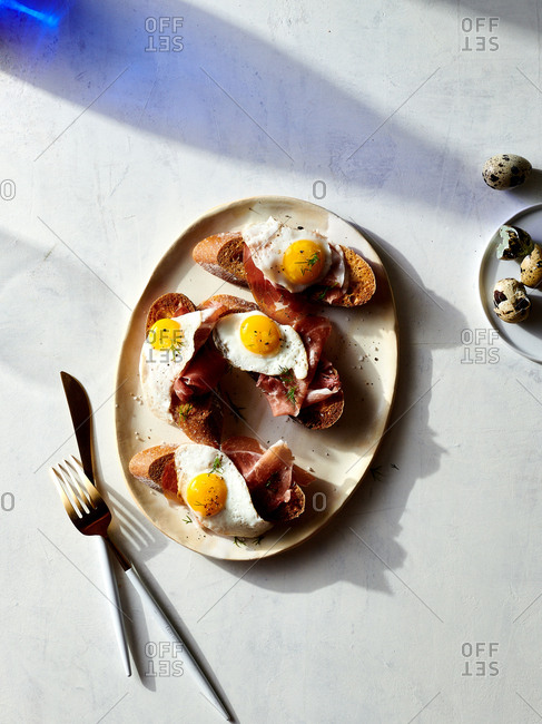 Overhead view of  a tray of quail egg toast with