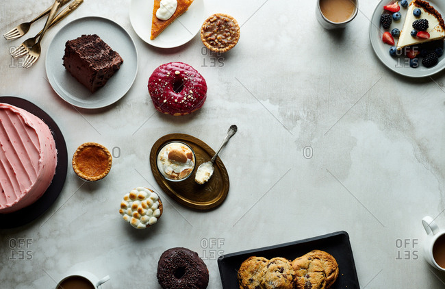 Overhead view of cakes, pies and cookies on a neutral table