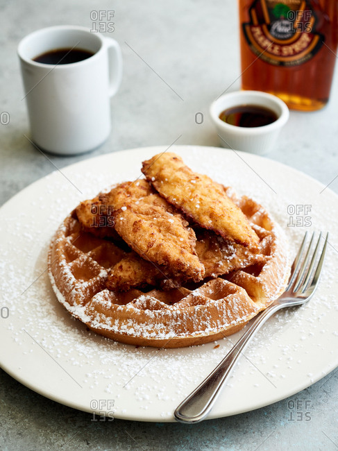Fried chicken and waffles dusted with powdered sugar