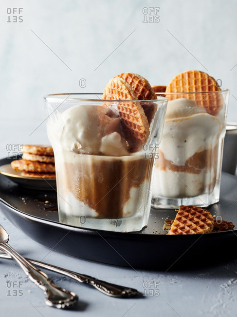 Close-up of two glasses of coffee, ice cream and cookies