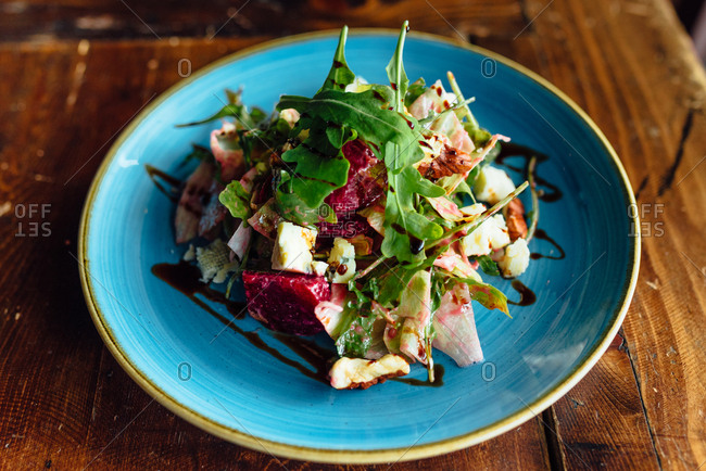 Chicken, beetroot and arugula salad on a blue plate