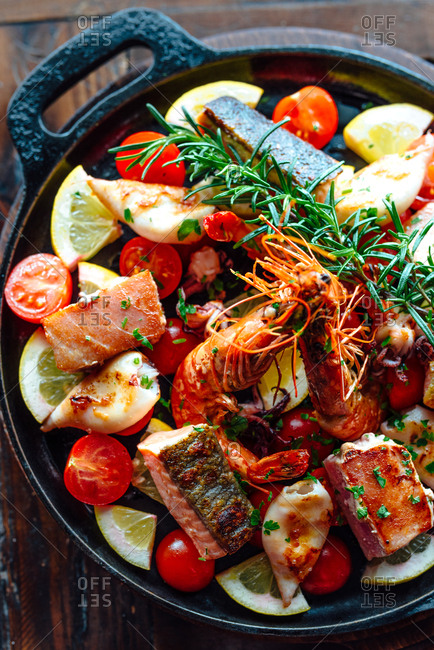 Prawns and salmon in a baking pan with lemon, rosemary and vegetables