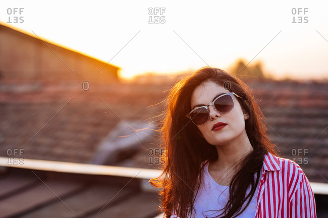 Portrait of beautiful young Caucasian woman with red lipstick and sunglasses standing against sunset.