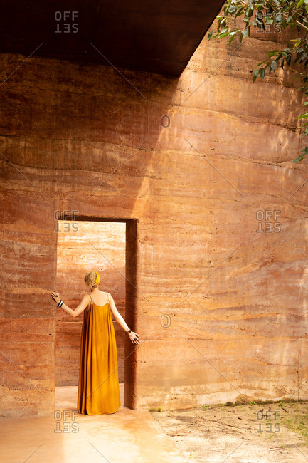 Back view of a woman in dress enjoying traveling and exploring unique architecture.