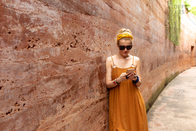 Beautiful blonde woman in summer dress standing by the rammed earth wall and typing on her cell phone.