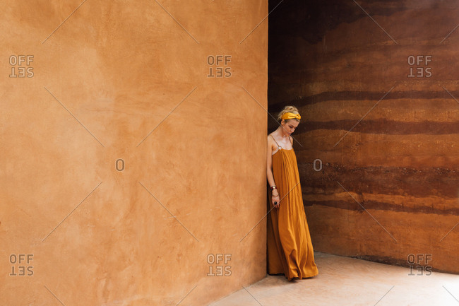 Portrait of beautiful woman in summer dress standing and posing by the rammed earth walls.