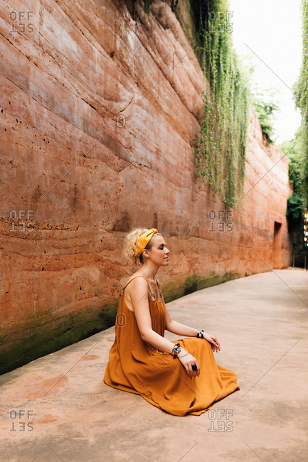 Beautiful woman in a dress sitting on the ground by the rammed earth wall and meditating.