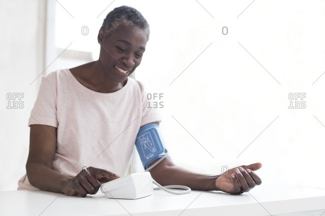 Mature woman testing blood pressure with machine.