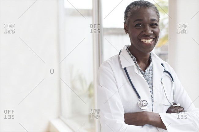 Mature female doctor smiling with arms crossed.
