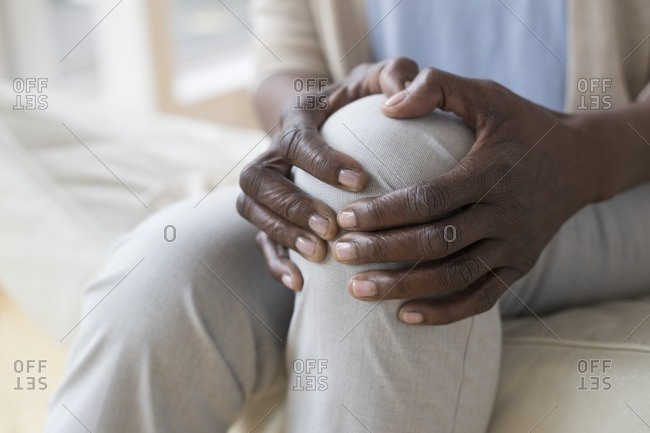 Mature woman holding sore knee.