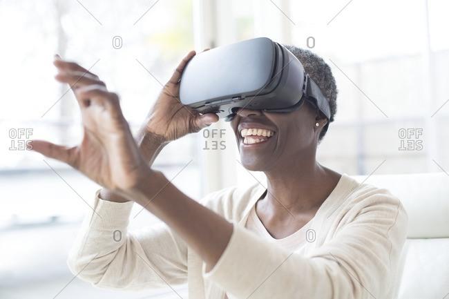 Mature woman wearing virtual reality headset and reaching.