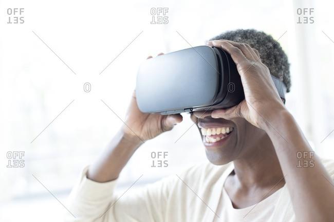 Mature woman wearing virtual reality headset.