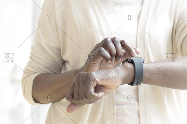 Mature woman wearing fitness watch.