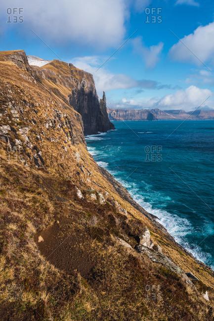 Waves of blue sea water splashing near rough rocky cliff on sunny day on Faroe Islands