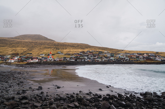 Water of beautiful sea rolling on wet shore near small coastal settlement and hill on cloudy day on Faroe Islands