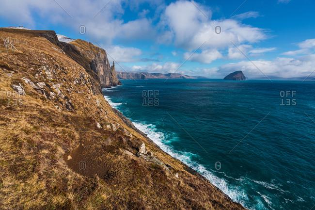 Waves of amazing blue sea rolling near rough rocky coast on cloudy day on Faroe Islands